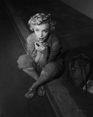 Marilyn Monroe oozes sex appeal in gingham capri pants and a simple shirt.